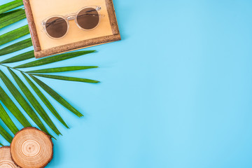 Wall Mural - summer blue banner with wood picture grame ,sunglasses,seashell and palm leaf on blue background top view.