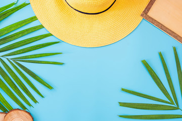 Wall Mural - summer blue banner with yellow hat ,sunglasses,seashell,frame and palm leaf on blue background top view.