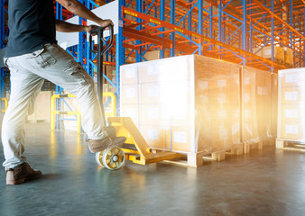 warehouse worker is working with hand pallet truck or pallet jack and shipment pallets.