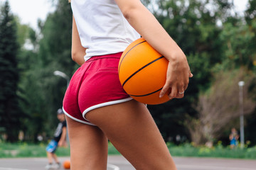 Young woman dressed in white t-shirt, shorts holding a ball on a basketball court.