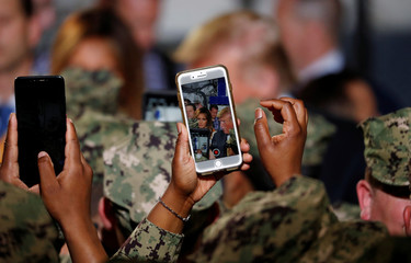 A soldier takes a photo as U.S. President Donald Trump and first lady Melania Trump interact with military personnel aboard the USS Wasp during a Memorial Day Address in Yokosuka