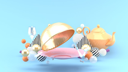Golden food cover, plate, wine glass and teapot surrounded by colorful balls on a blue background.-3d rendering.