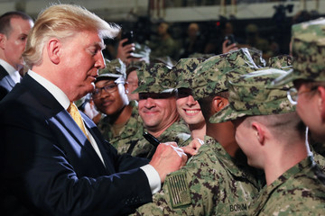U.S. President Donald Trump signs a dollar bill for a troop member aboard the USS Wasp in Yokosuka
