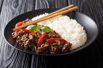 Fototapeta Traditional Thai Basil Beef, or Pad Gra Prow over white rice closeup on a plate. horizontal obraz