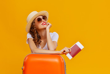 concept of travel. happy woman girl with suitcase and  passport on  yellow background. Fotomurales