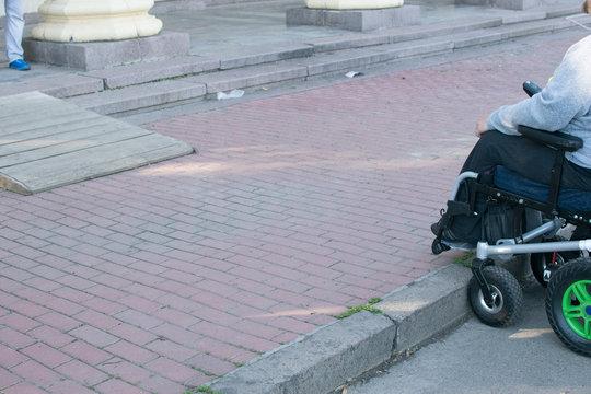 a person in an electric wheelchair near a sidewalk
