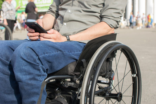a man in a wheelchair with a phone in his hands