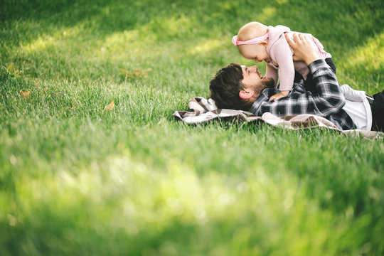 Father and his little baby daugter reading book sitting on a green grass in a park.
