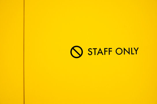 sign of staff only on yellow wall