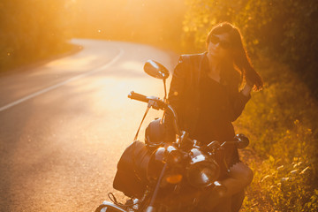 La pose en embrasure Motocyclette attractive brunette motorcyclist standing near a motorcycle On the Sunset. adventure concept