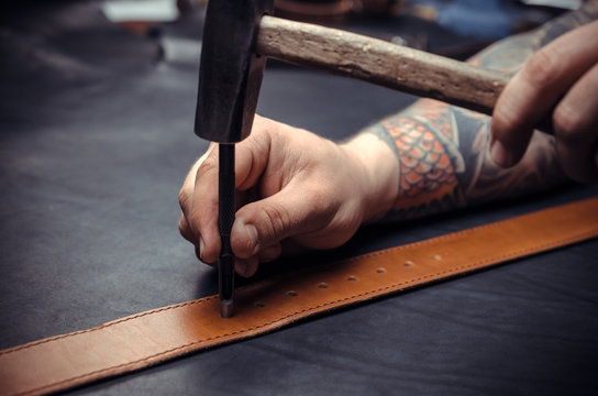 Professional Leather Worker cuts out leather goods at his tanning shop