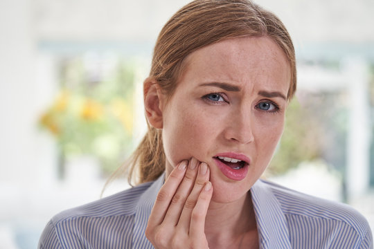 Portrait Of Young Woman Suffering With Toothache Touching Jaw