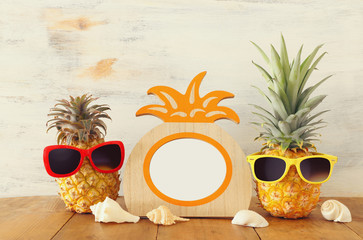 Empty photo frame and couple of funny pineapple with sunglasses. For photography and scrapbook montage