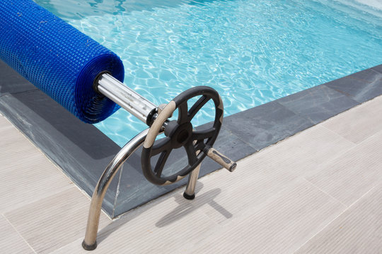 swimming pool with blue bubble cover winder and steering wheel