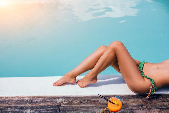 Beautiful woman legs. Sunbathing near swimming pool.