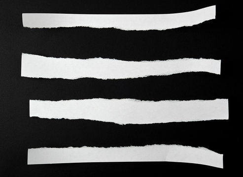 torn blank white paper strips against a black background