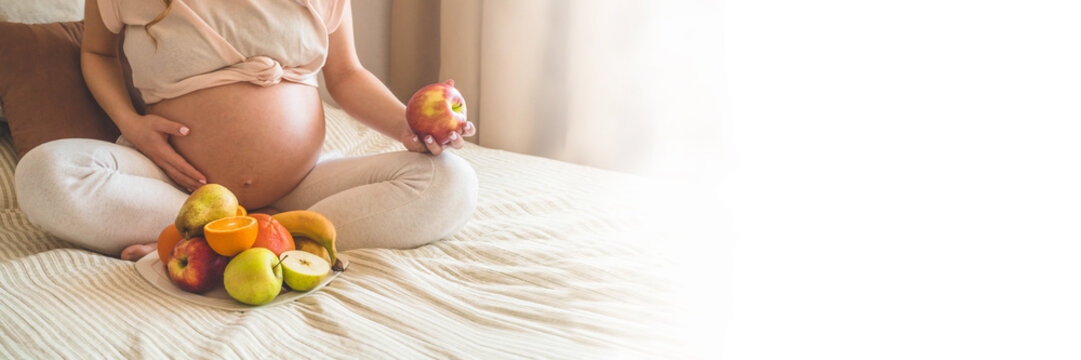 Pregnancy and healthy organic nutrition. Pregnancy and grapefruit. Pregnant woman enjoying fresh fruits in bed, free space. Concept of expectation and health