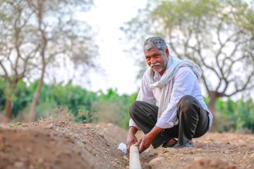 Indian / Asian Farmer checking water tube at field  Wall mural