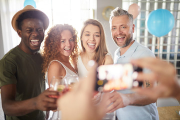 Multi-ethnic group of people smiling cheerfully to camera while posing for photo during party, copy space