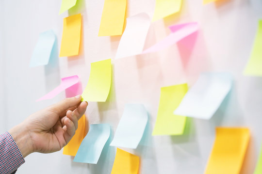close up hand people business man  notes pad in the wall at meeting room. Sticky post it note paper reminder schedule board. Colorful variety copy empty space. soft focus.