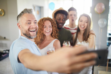 Multi-ethnic group of people smiling cheerfully to camera while posing for selfie photo during party, focus on mature man in foreground, copy space