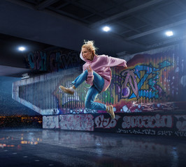 Female Hip Hop Dancer. Beautiful girl dancing at night on the background of graffiti wall