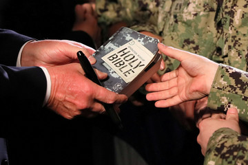 A U.S. Navy sailor hands his Bible to U.S. President Trump to autograph as he greets sailors after his speech aboard the USS Wasp at JMSDF Yokosuka base in Yokosuka, south of Tokyo