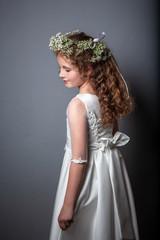 Caucasian girl wearing first holy communion dress. Girl preparing to take first communion. First Communion Day. Studio photo