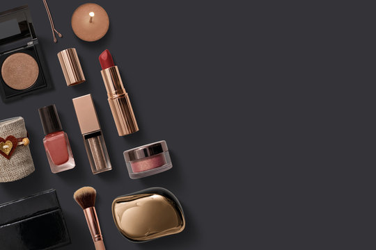 various makeup objects with golden tones on dark background