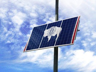 Solar panels against a blue sky with a picture of the flag State of Wyoming
