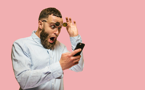 Shocked hipster man hold on eye glasses and looking at the phone. emotional male can't believe in sales in web store. blank space for your text.