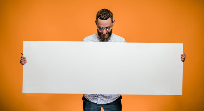 Hipster man holding a poster with blank space for your text.