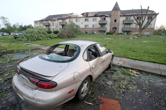 A damaged car is parked in front of an apartment building after a tornado touched down overnight in Trotwood