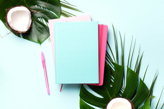 Female blog writer workspace concept. Green monstera palm leaves, coconut on pink background with copy space. Banner. Flat lay, top view.