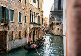 Photo sur Aluminium Gondoles Venetian gondolier punts gondola through narrow canal waters of Venice Italy