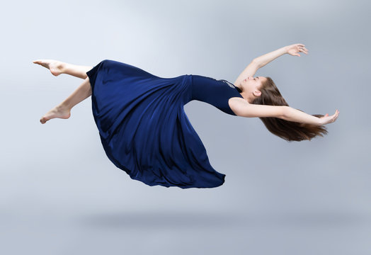A girl in a blue dress is floating in the air. Dress and hair fluttering in the wind. Flight. Fantasy.
