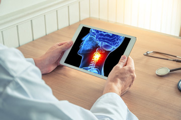 Doctor holding a digital tablet with x-ray of  3D skull with pain on the neck. Headache migraine or trauma concept