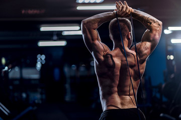 Hard working well built sportsman exercising with a resistance band in gym Wall mural