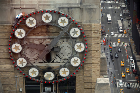 A worker climbs on a clock while replacing lightbulbs above Times Square on the Paramount building in New York