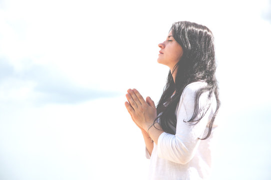 Praying hands with faith belief in God. A woman praying. Closed her eyes. Against the background of sky and clouds.