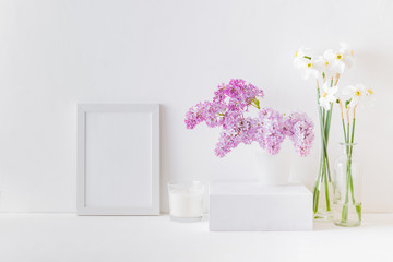 Home interior with decor elements. White frame, white daffodils in a vase, interior decoration