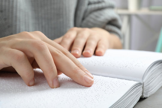 Blind person reading book written in Braille, closeup