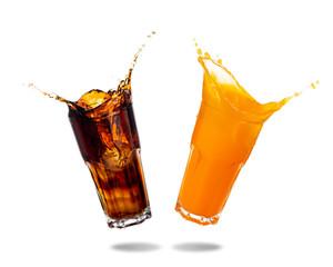 Cola and orange soda splashing out of glass isolated on white background.