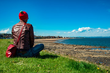 Scenic view of Portobello beach with a tourist. Edinburgh, Scotland, UK.
