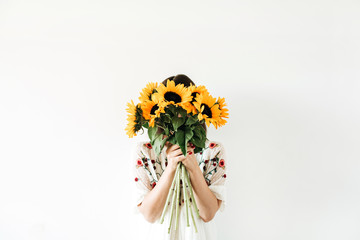 Young pretty woman with sunflowers bouquet on white background.