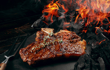 barbeque steak on a black slate board with meat fork and grill coals next to it Wall mural
