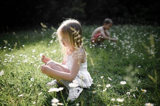 Children plucking flowers in field