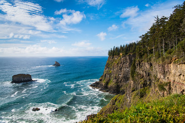 A coastline of high, green forested cliffs with a beautiful blue sea and sky - Cape Meares on the Oregon coast