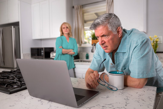 Senior husband stressed expression while using laptop computer, retirement financial issues