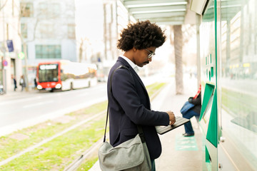 Spain, Barcelona, businessman using ticket machine at tram stop in the city
